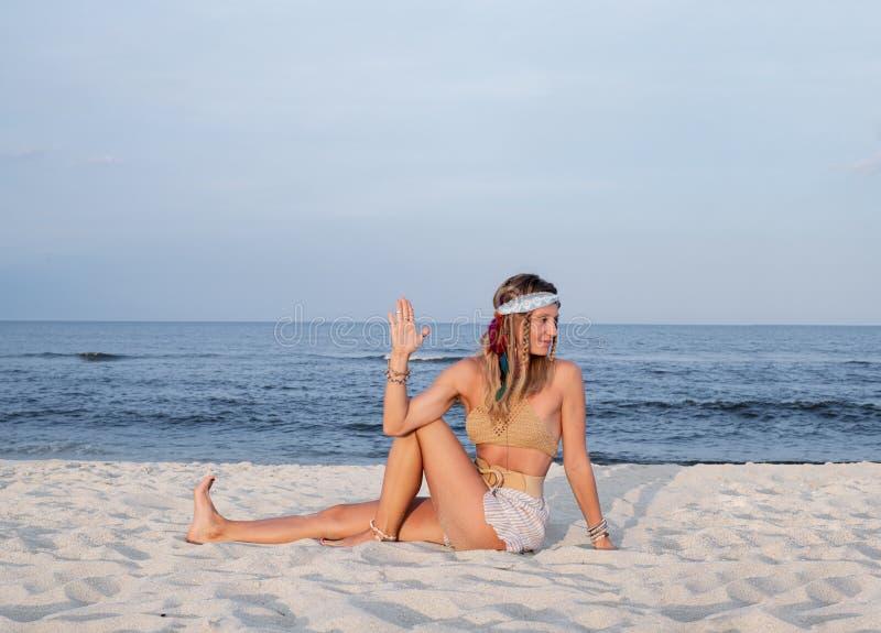 Young woman practicing yoga on the beach. Ardha Matsyendrasana pose royalty free stock photos