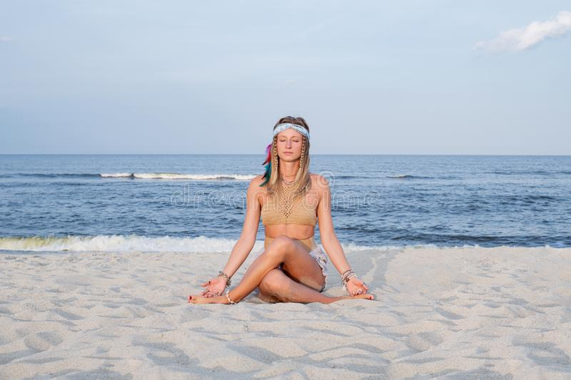 Young woman practicing yoga on the beach in Gomukasana pose royalty free stock images