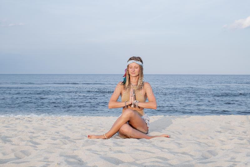 Young woman practicing yoga on the beach in Gomukasana pose stock photo
