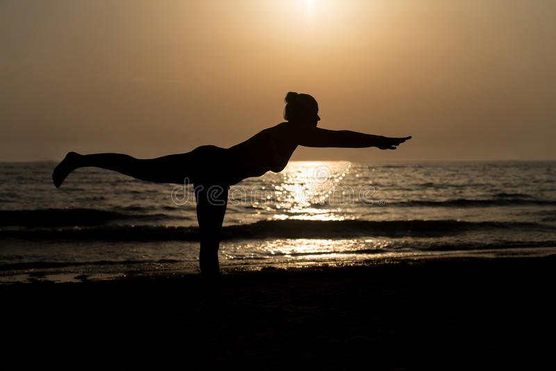 Young Woman Practicing Yoga on the Beach royalty free stock photography