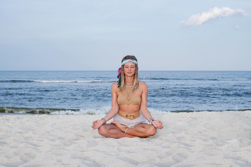 Young woman practicing yoga on the beach. Lotus pose stock photo