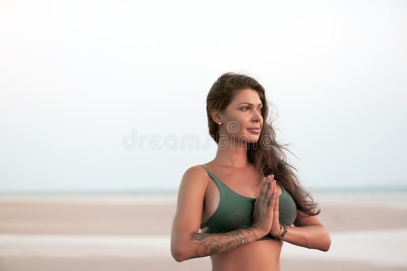 Young woman practicing yoga on the beach at sunset stock photography