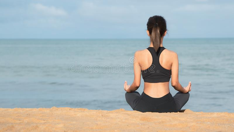 Young woman practicing yoga on the beach at sunset. Meditation, Young healthy woman practicing yoga on the beach at sunrise. stock photo