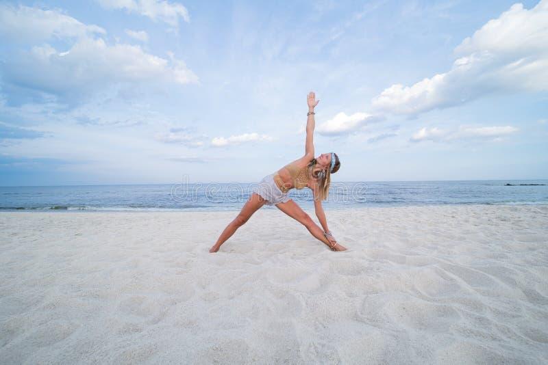 Young woman practicing yoga on the beach. Utthita Trikonasana pose royalty free stock images