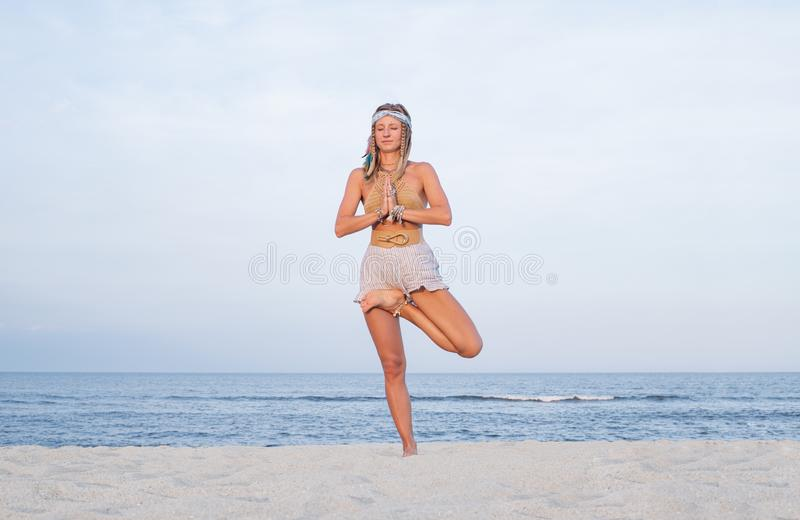 Young woman practicing yoga on the beach. Vrksasana pose stock image