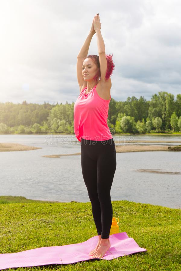 Young woman practicing yoga in beautiful nature. Lake shore in morning sunny day stock photography