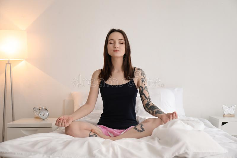 Young woman practicing yoga on bed in morning stock image