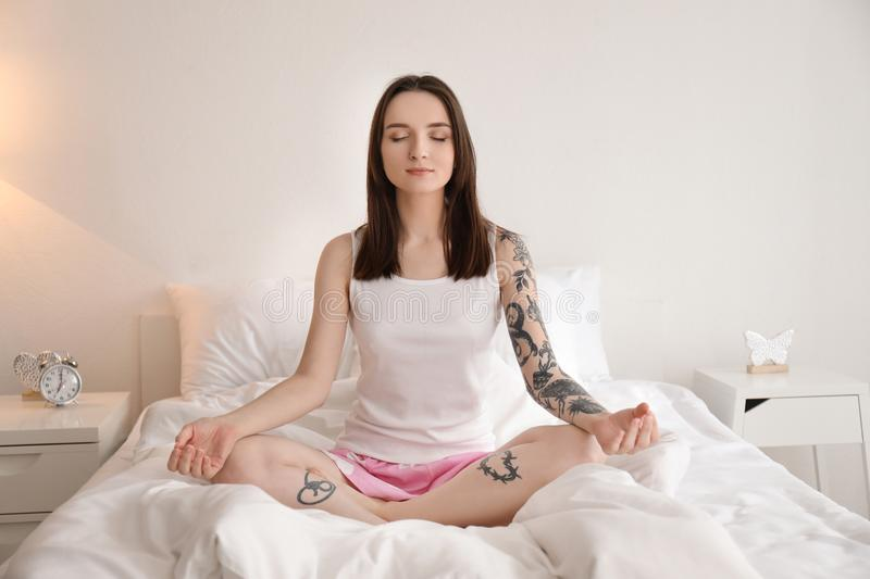 Young woman practicing yoga on bed in morning royalty free stock photos