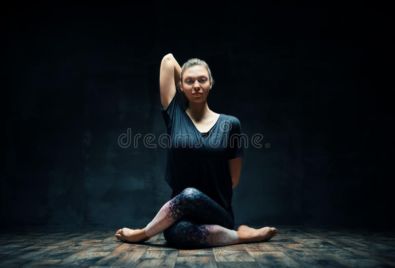 Young woman practicing yoga doing Gomukhasana, cow face pose, in dark room. Wellbeing, meditation and healthy lifestyle royalty free stock images