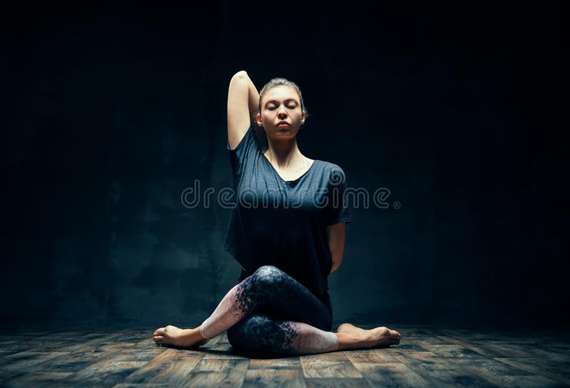 Young woman practicing yoga doing Gomukhasana, cow face pose, in dark room. Wellbeing, meditation and healthy lifestyle royalty free stock photo