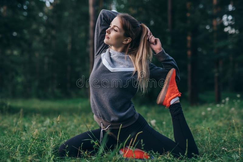 Young woman practicing yoga doing one-legged pigeon pose sitting on grass in park royalty free stock photos