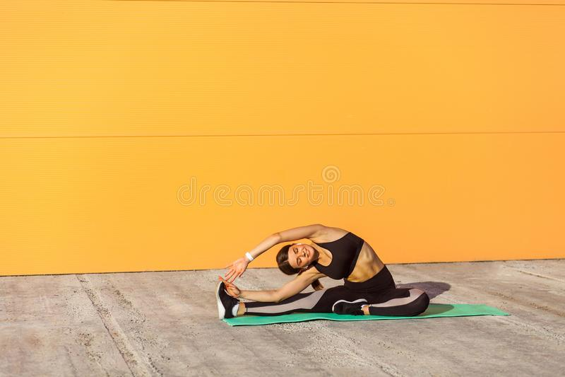 Young woman practicing yoga, doing revolved head to knee forward exercise, parivrtta janu sirsasana pose stock photos