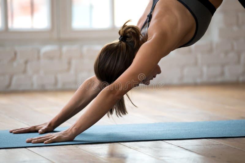 Young woman practicing yoga, Downward facing dog exercise close. Young sporty woman practicing yoga, doing Downward facing dog exercise, adho mukha svanasana stock photo