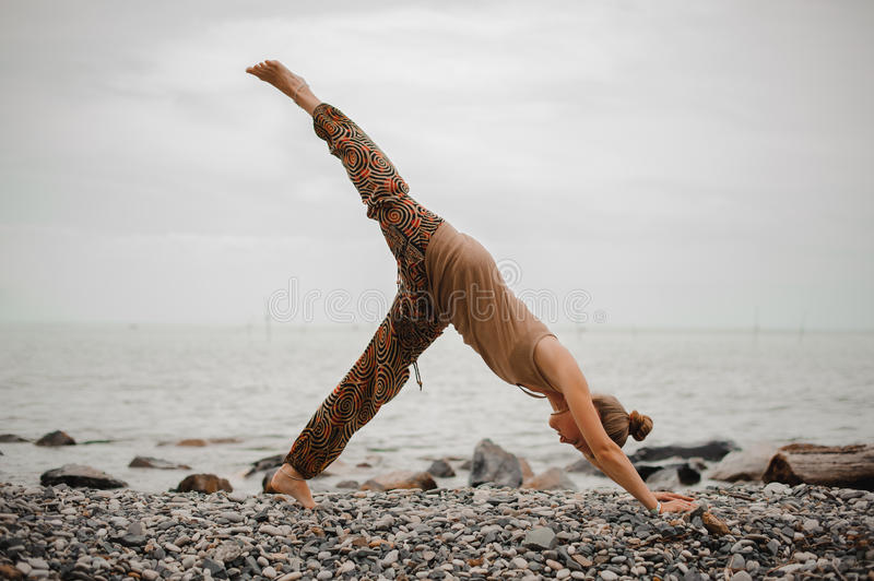 Young woman practicing yoga in downward facing dog pose on beach stock photos