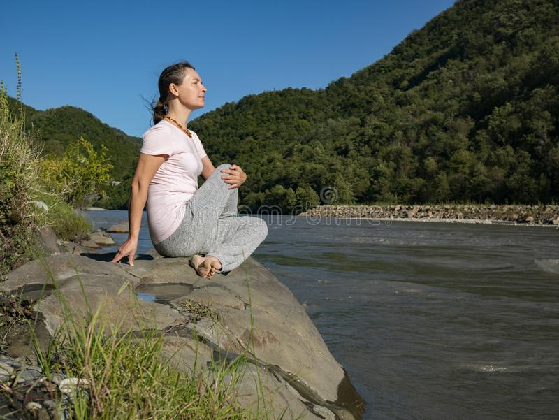 Young woman is practicing yoga in Half Lord of the Fishes Pose Matsyendra pose at mountain lake.  royalty free stock photography