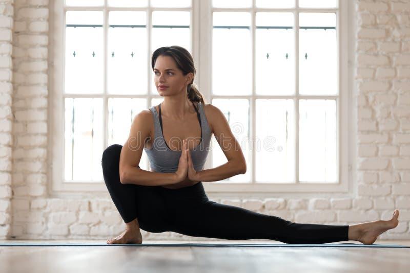 Young woman practicing yoga, Janu Sirsasana pose stock image