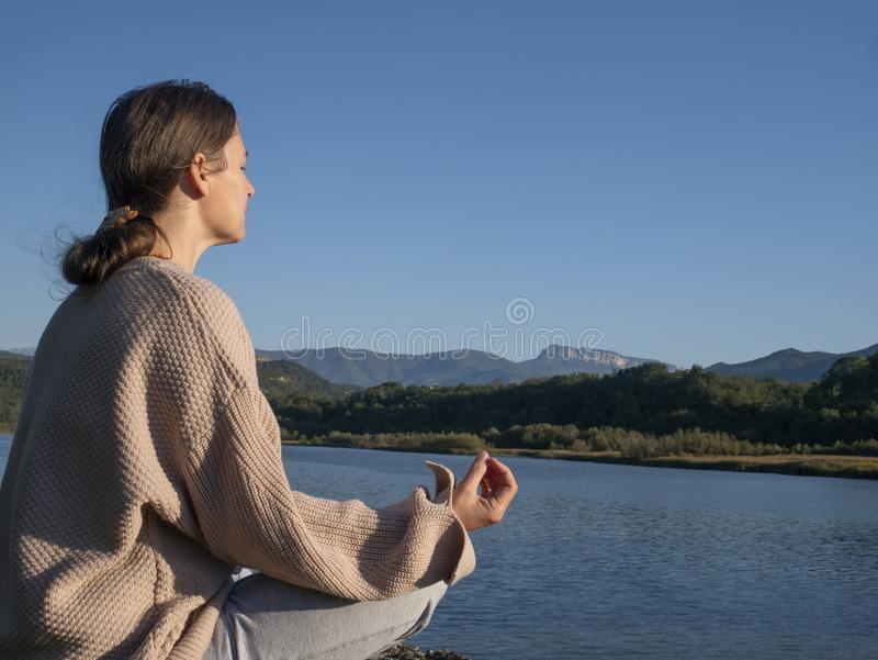 Young woman is practicing yoga in lotus pose at mountain lake royalty free stock photography