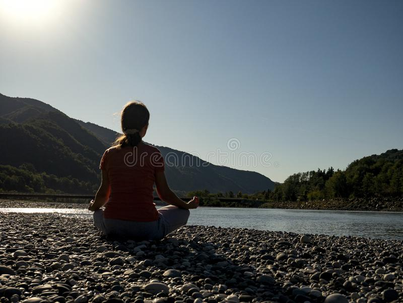Young woman is practicing yoga in lotus pose at mountain lake stock image