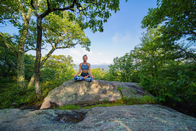 Young woman practicing yoga in lotus pose outdoors harmony with nature stock photo
