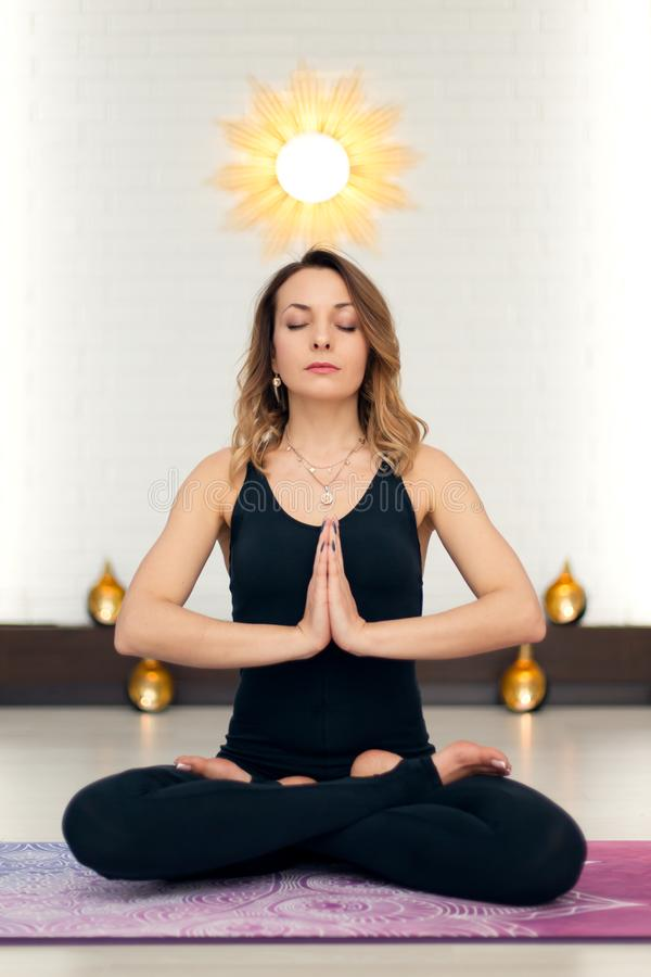 Young woman practicing yoga meditation in gym. Fit and wellness lifestyle stock image