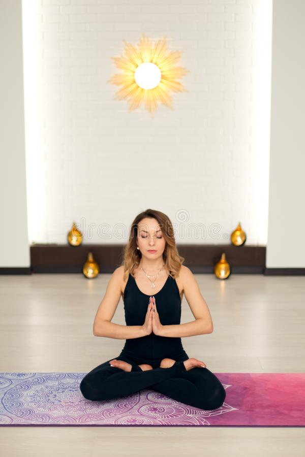 Young woman practicing yoga meditation in gym. Fit and wellness lifestyle stock images