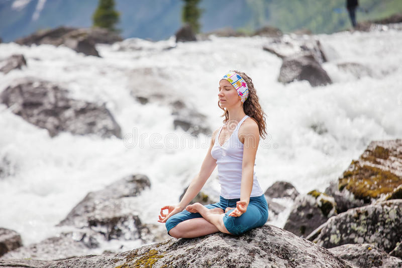 Young woman is practicing yoga at mountain river.  royalty free stock images