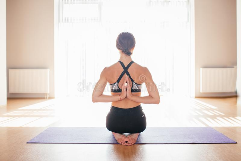 Young woman practicing yoga with namaste behind back at home indoor. Girl doing reverse prayer pose, back and shoulders stretching stock photos