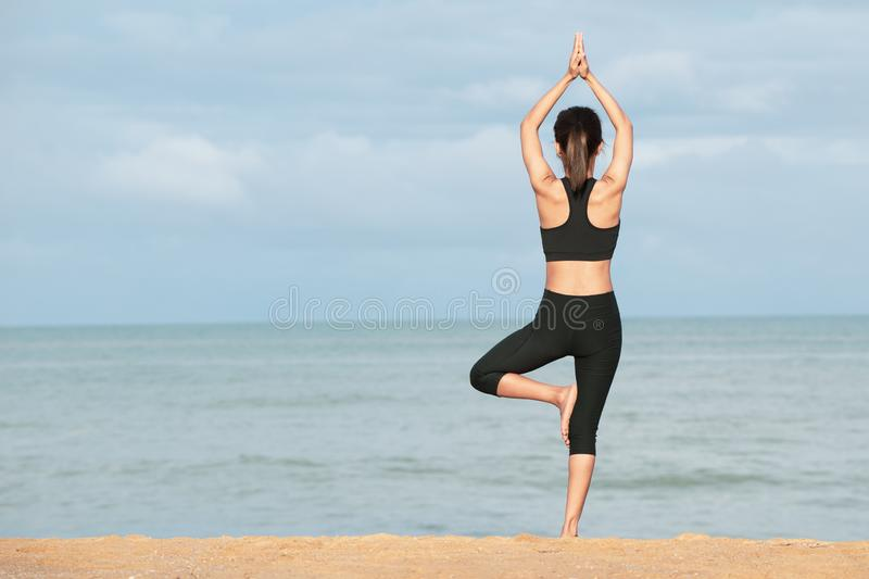 Young woman practicing yoga in the nature, Female happiness, Young woman practicing yoga on the beach stock photo