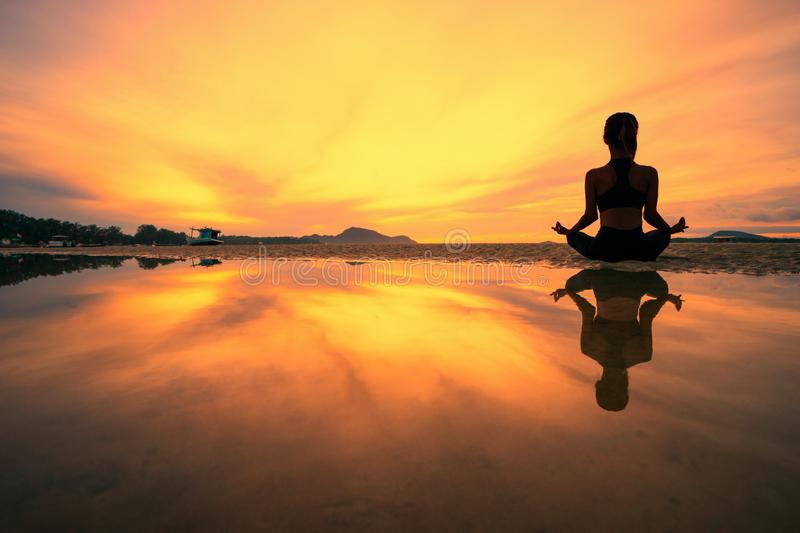 Young woman practicing yoga in the nature, Female happiness, Silhouette of young woman practicing yoga on the beach at sunset royalty free stock image