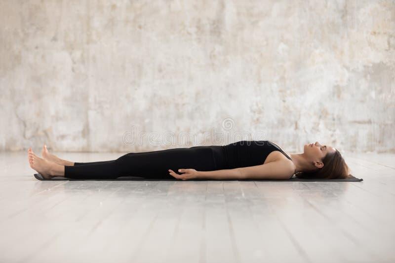 Young woman practicing yoga, Savasana, Dead Body pose, Corpse stock photo