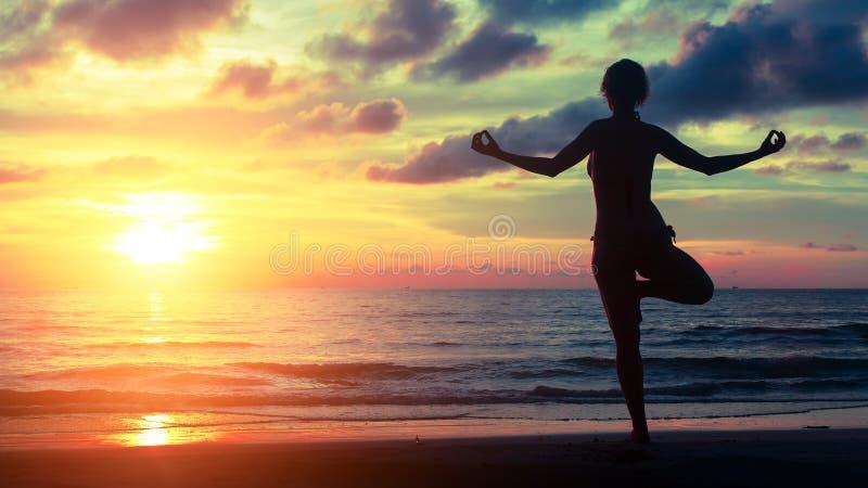 Young woman practicing yoga on the sea beach stock photos