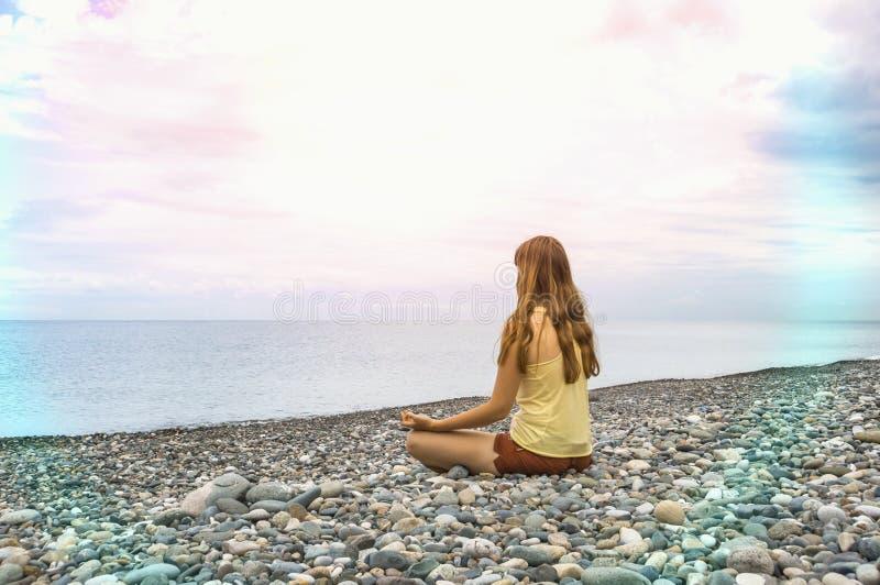 Young woman practicing yoga at seashore royalty free stock images