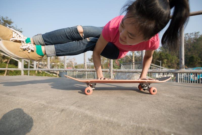 Woman practicing yoga on skateboard at skatepark ramp. Young woman practicing yoga on skateboard at skatepark ramp stock photography