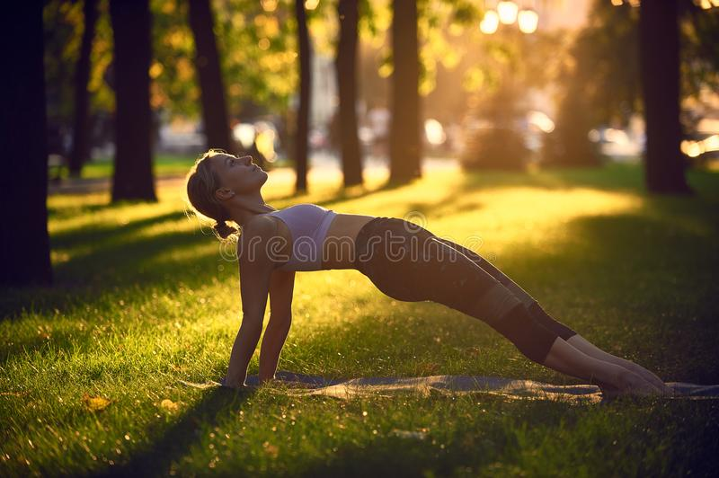 Young woman practicing yoga, stretching in Purvottanasana exercise - Upward Plank pose in the park at sunset royalty free stock photos