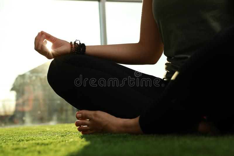Young woman practicing yoga in sunlit room. Closeup royalty free stock photos