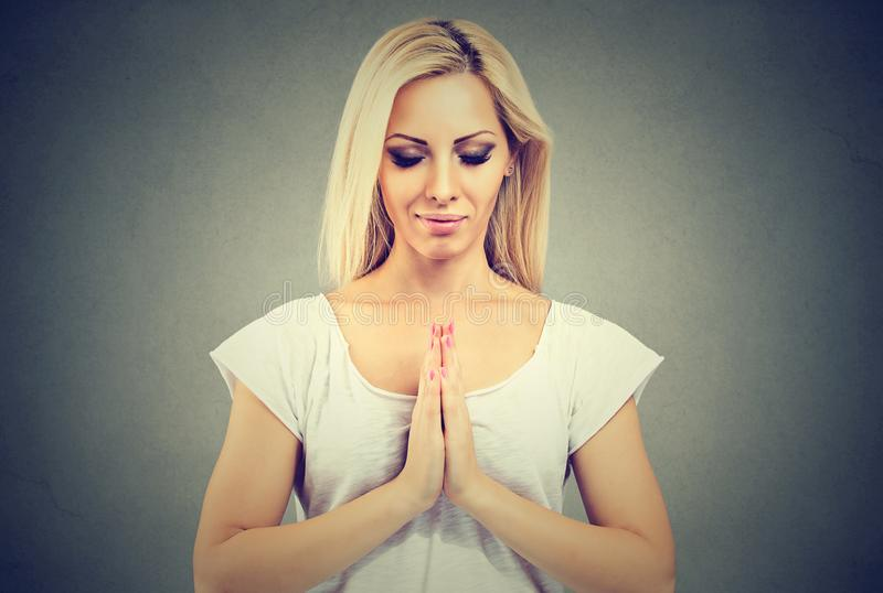 Young woman in a prayer position meditating stock images