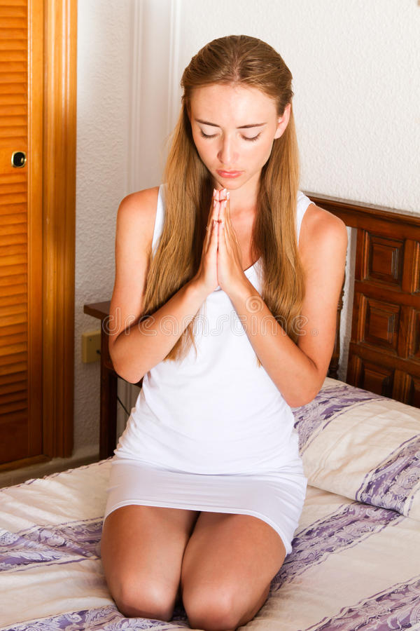Young woman praying on a bed royalty free stock images