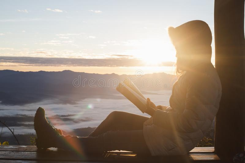 Young woman praying With the Holy Bible in the morning, Woman praying with hands together on the Sunrise background.  stock photography