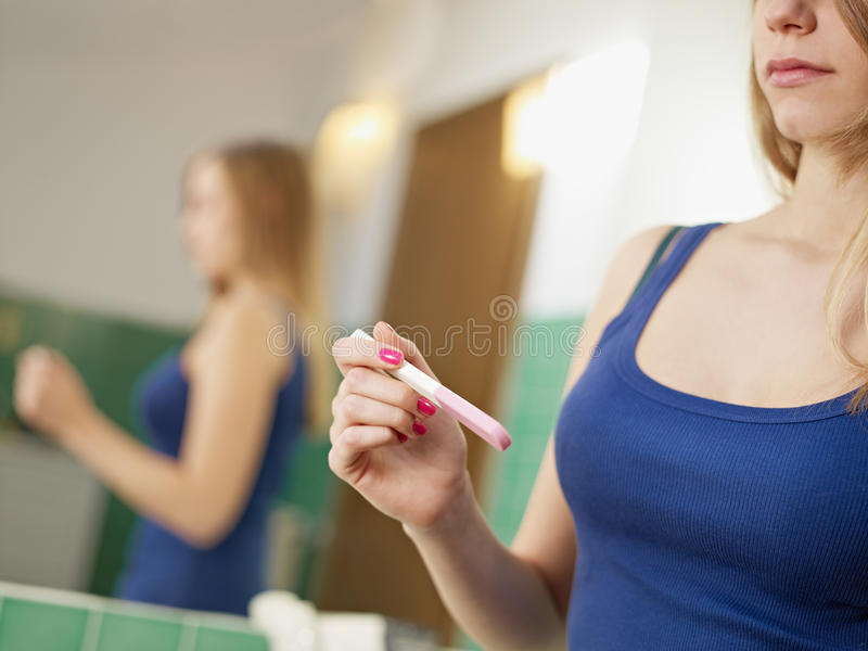 Young woman with pregnancy test kit stock images