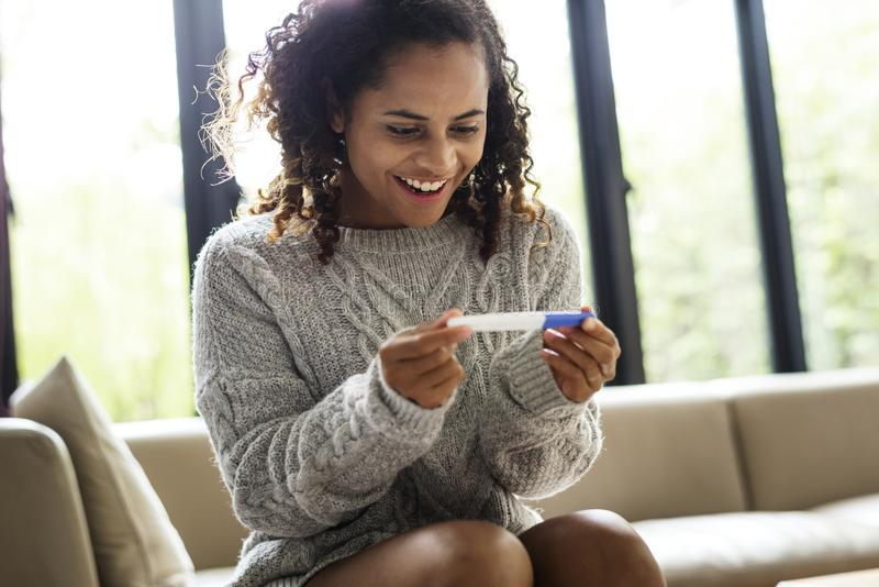 A young woman with a pregnancy test stock images