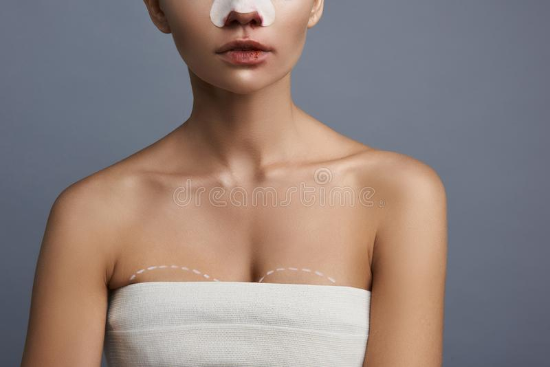Young woman preparing for breast augmentation and wearing white towel royalty free stock photos