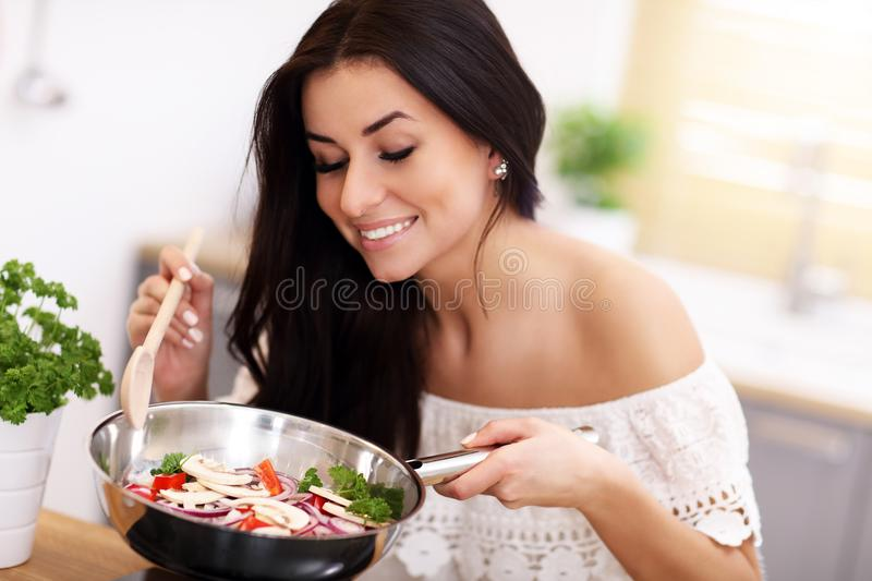 Young woman preparing fried vegetables in kitchen stock image