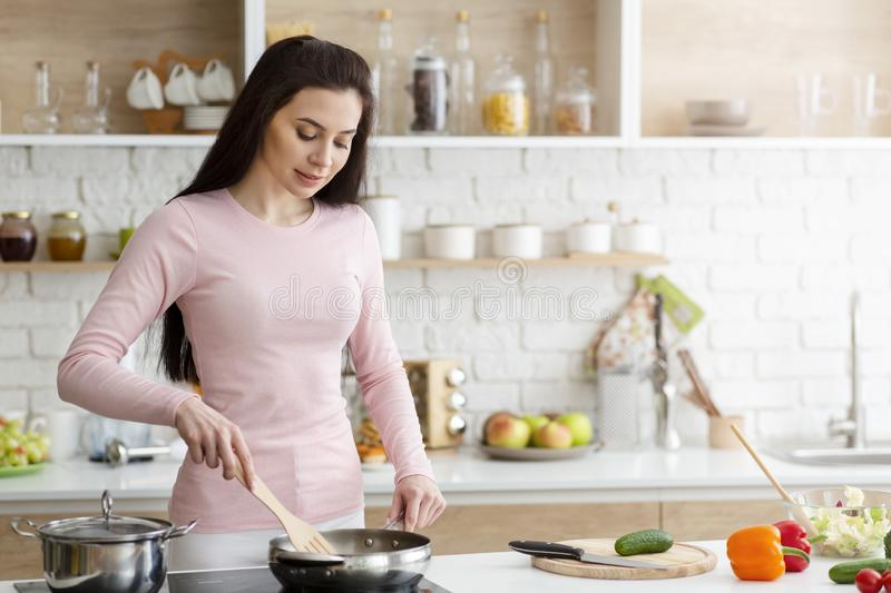Young woman preparing meal on stove at home royalty free stock photos