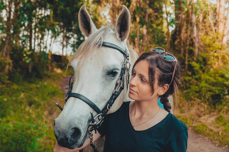 Young woman preparing to become a riding instructor taking care and talking to a horse on a hot autumn day royalty free stock images