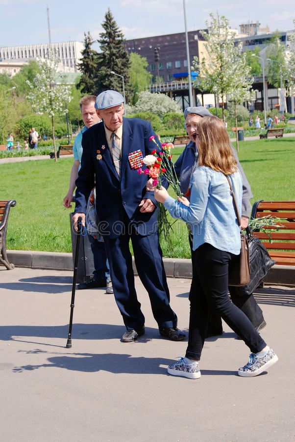 A young woman present flowers to war veterans. MOSCOW - MAY 09, 2016: A young woman present flowers to war veterans. Victory Day celebration in Gorky park in stock images