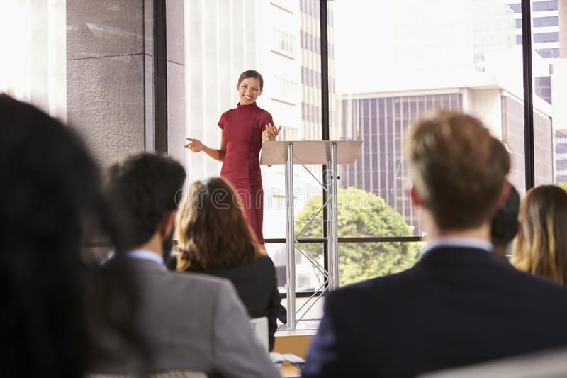 Young woman presenting business seminar gestures to audience. Young women presenting business seminar gestures to audience stock photos