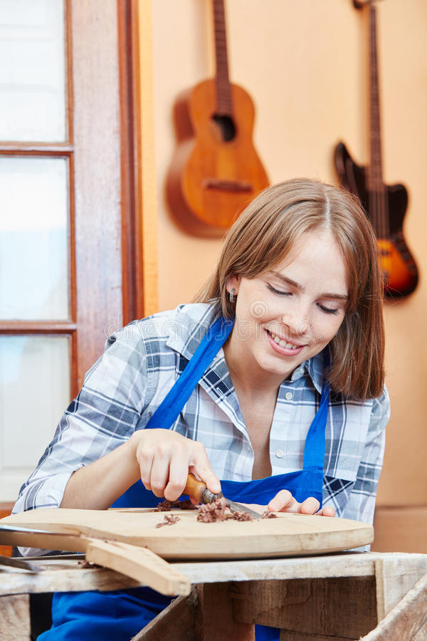 Young woman processing wood. In luthier apprenticeship royalty free stock photos