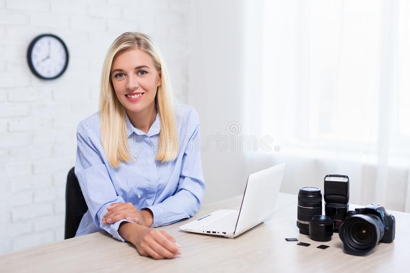 Young woman professional photographer with camera, computer and photography equipment working in office royalty free stock images