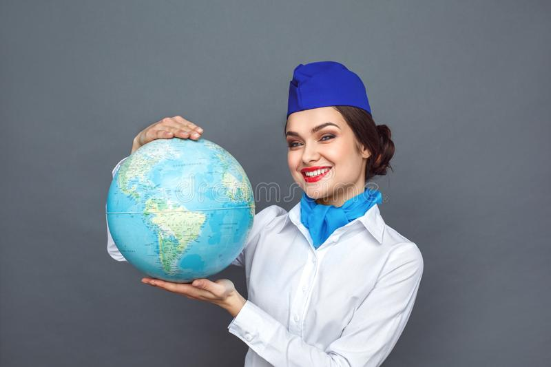Professional Occupation. Stewardess standing isolated on grey showing globe looking camera cheerful close-up stock photos