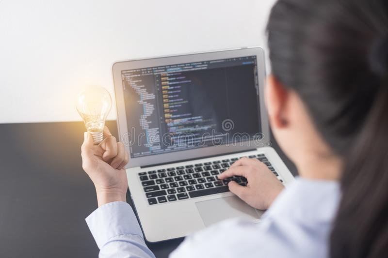 Young woman programmer hand holding light bulb, woman hands coding and programming on screen laptop, new ideas with innovation. royalty free stock photos